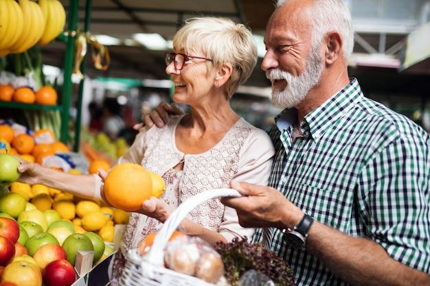 Glimlachend senior paar met mand met groenten in de supermarkt