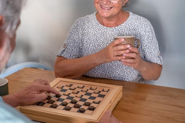 Glimlachend senior paar thuis spelen met dammen op houten tafel. zelfisolatie of lockdown