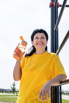 Glimlachend senior vrouw drinkwater na training buiten op het sportveld