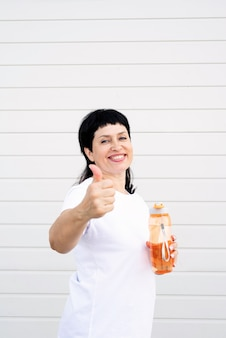 Glimlachend senior vrouw drinkwater na training buiten op stedelijke scène