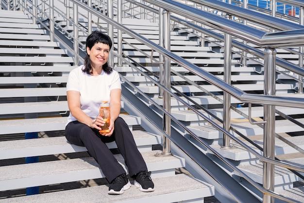 Glimlachend senior vrouw drinkwater na training buitenshuis