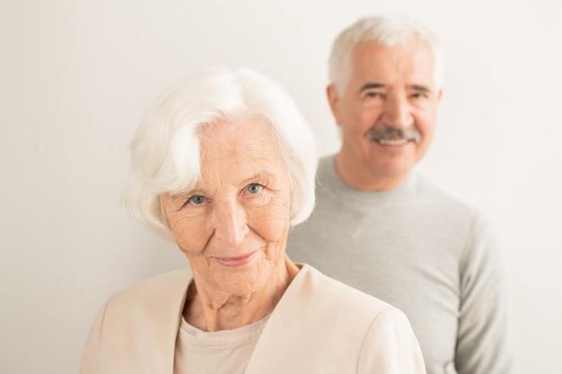 Glimlachend senior vrouw met wit haar op zoek naar jou terwijl ze met haar man staat