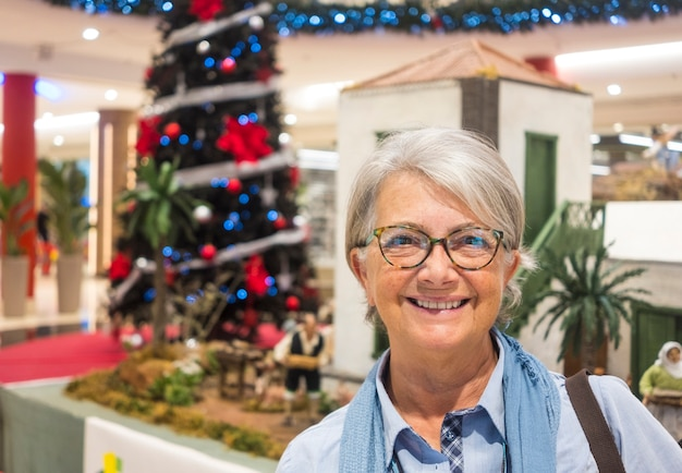Glimlachend senior vrouw wit haar en bril permanent in winkelcentrum met kerstboom op achtergrond - concept van vakantie en consumentisme