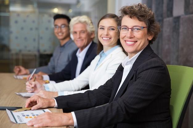 Glimlachend senior zaken tijdens de bijeenkomst met team