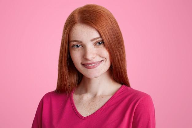 Glimlachend sproeterig vrouwtje met recht luxueus rood haar, blij met een goed voorstel voor een baan