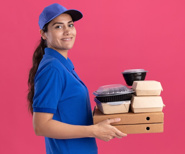 Glimlachend staand in profiel bekijken jong bezorgmeisje die uniform met pet dragen die voedselcontainers op pizzadozen houden die op roze muur worden geïsoleerd