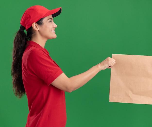 Glimlachend staand in profielweergave jong bezorgmeisje met uniform en pet die papieren voedselpakket geeft aan klant geïsoleerd op groene muur