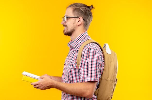 Glimlachend staande in profiel bekijken jonge kerel student draagt rugzak met bril met boek