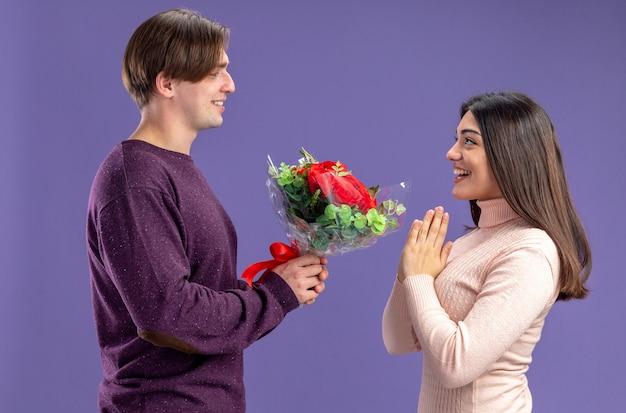 Glimlachend staande in profiel weergave jong koppel op valentijnsdag man boeket geven aan meisje geïsoleerd op blauwe achtergrond