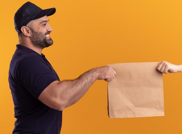Glimlachend staande in profielweergave bezorger van middelbare leeftijd in uniform en pet die papieren voedselpakket geeft aan klant geïsoleerd op gele muur