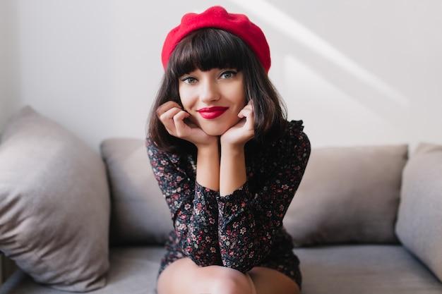 Glimlachend stijlvol frans meisje zittend op een grijze bank en houdt haar kin met haar handen, camera kijken. aantrekkelijke jonge vrouw in trendy vintage outfit poseren tijdens het rusten thuis in lichte kamer