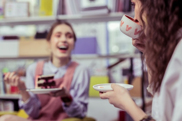 Glimlachend stralend meisje. lachende vrolijke dames die thee drinken en een toetje eten tijdens een rustige tijd met een goede vriend