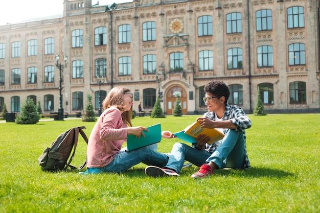 Glimlachend studenten afrikaans amerikaans mannetje in glazen met boeken en een meisje dichtbij universiteit.