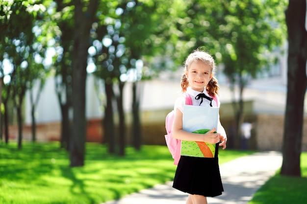Glimlachend studentenmeisje die schoolrugzak dragen en oefenboek houden. portret van gelukkig kaukasisch jong meisje buiten de basisschool. glimlachend schoolmeisje