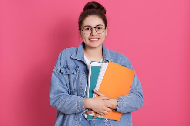 Glimlachend studentenwijfje met donker haar en knoop, die document omslagen houden