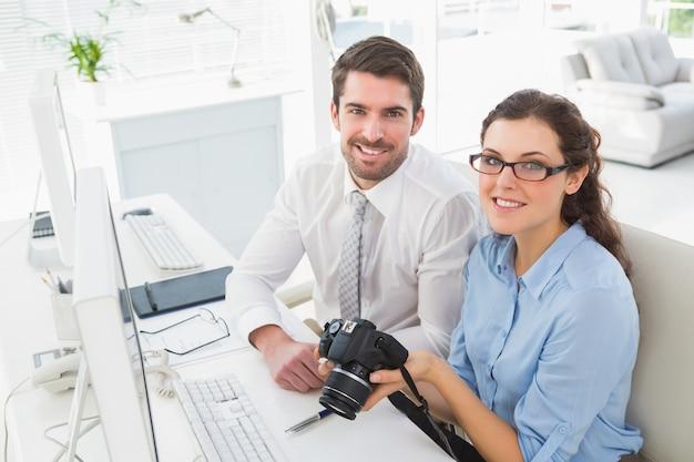 Glimlachend team dat digitale camera houdt