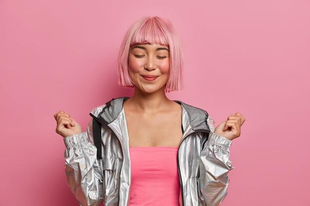 Glimlachend tevreden aziatisch meisje met kort roze haar, natuurlijke schoonheid, sluit ogen, steekt handen gebalde vuisten op, voelt zich erg gelukkig, gekleed in modieuze zilveren jas,