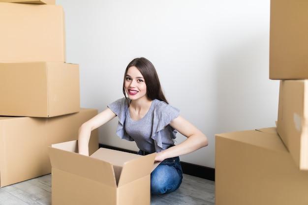 Glimlachend tevreden jonge vrouw klant zitten op de bank pakket open pakket uitpakken, gelukkig meisje consument met kartonnen doos ontvangen goede online winkel aankoop thuis, post post verzending leveringsconcept