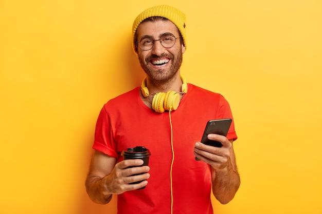 Glimlachend tevreden mannetje verspilt tijd in sociale netwerken, bladert op internet op mobiele telefoon, drinkt koffie uit een afhaalbeker, heeft zorgeloze, vreugdevolle uitdrukking