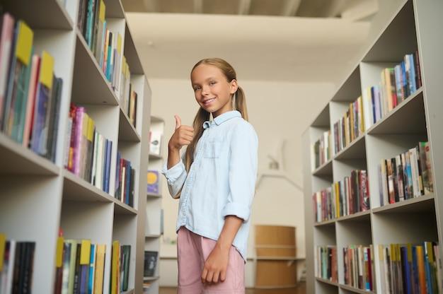 Glimlachend tevreden mooie scholier met paardenstaarten gekleed in vrijetijdskleding die in de buurt van boekenplanken in de bibliotheek staat