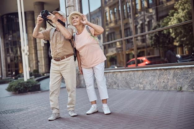 Glimlachend tevreden stijlvolle blanke senior vrouwelijke toerist die bij haar man staat met een digitale camera