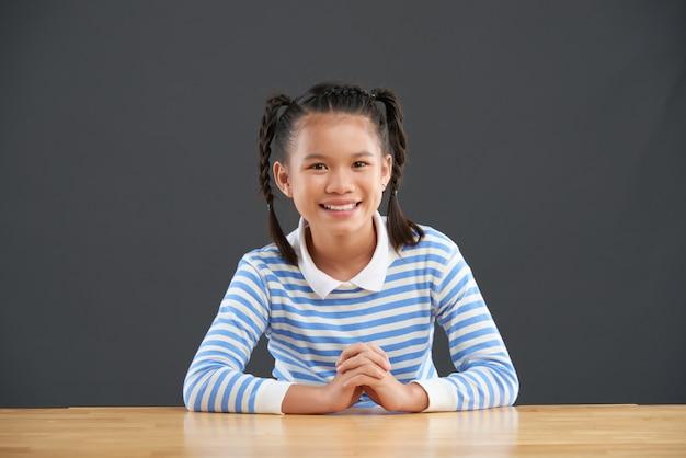 Glimlachend tiener aziatisch schoolmeisje dat met vlechten bij bureau zit