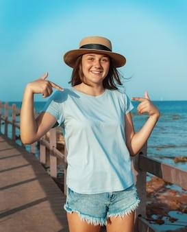 Glimlachend tienermeisje dat op een houten stoep aan zee blijft met een strohoed, een lichtblauw t-shirt en ernaar wijst. t-shirtmodel
