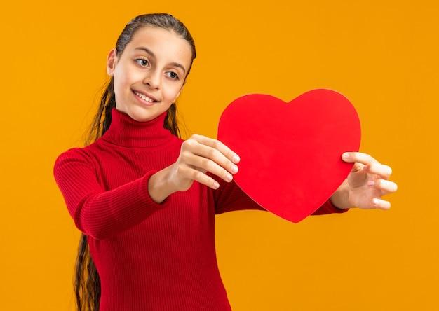 Glimlachend tienermeisje dat zich uitstrekt en kijkt naar hartvorm geïsoleerd op oranje muur