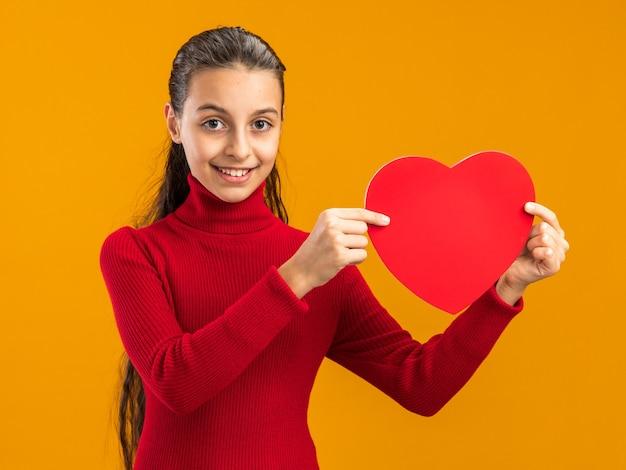 Glimlachend tienermeisje die hartvorm toont aan camera die naar voorzijde kijkt die op oranje muur wordt geïsoleerd