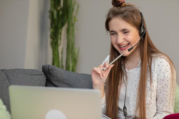 Glimlachend tienermeisje die hoofdtelefoons dragen die aan audiocursus luisteren die laptop thuis met behulp van, nota's maken, jonge vrouw die vreemde talen leren, digitaal zelfonderwijs, online bestuderen