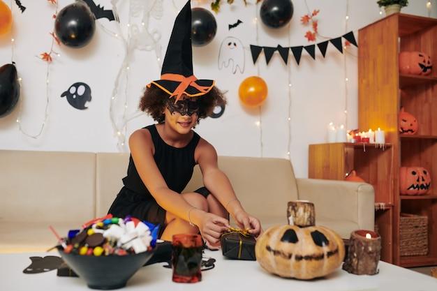 Glimlachend tienermeisje in komische heksenhoed versieren tafel voor halloween party