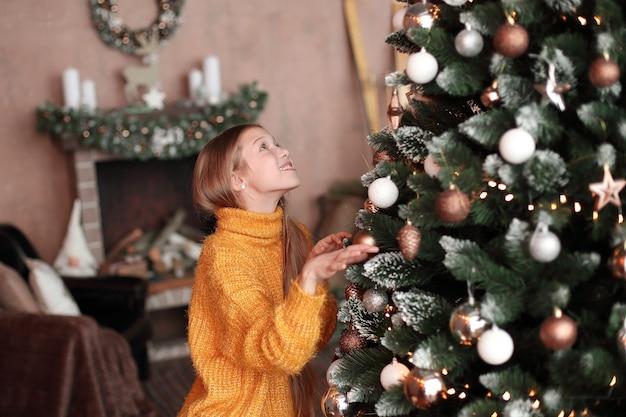 Glimlachend tienermeisje kerstboom in gezellige woonkamer versieren.