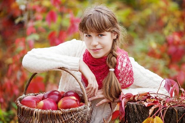 Glimlachend tienermeisje met mand met appels in de herfsttuin. peuter die fruit eet bij de herfstoogst. buitenpret voor kinderen. gezonde voeding