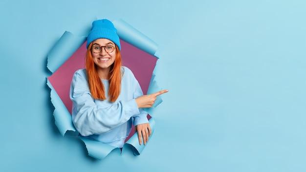 Glimlachend tienermeisje met rood haar geeft aanbeveling, wijzend op kopie ruimte, breekt door blauw papier gat
