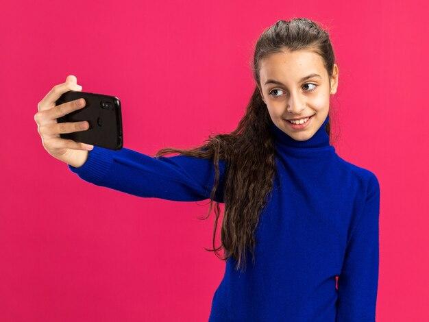 Glimlachend tienermeisje nemen selfie geïsoleerd op roze muur
