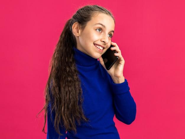 Glimlachend tienermeisje staande in profielweergave praten aan de telefoon kijkend naar kant geïsoleerd op roze muur met kopieerruimte