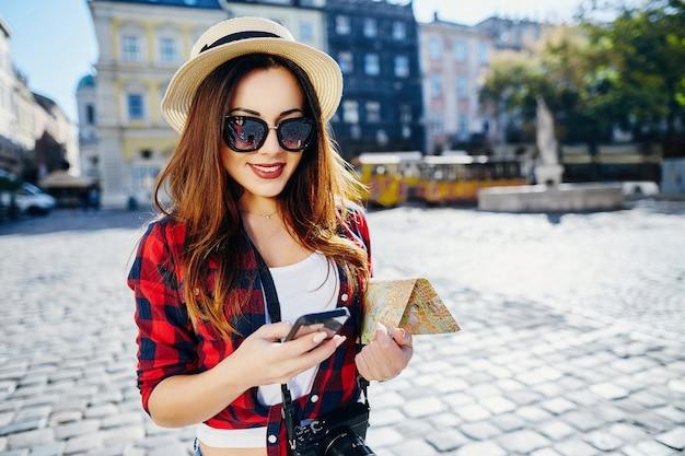 Glimlachend toeristenmeisje met bruin haar dat hoed, zonnebril en rood overhemd draagt, kaart bij oude europese stadsachtergrond houdt en glimlacht, reist, mobiele telefoon.