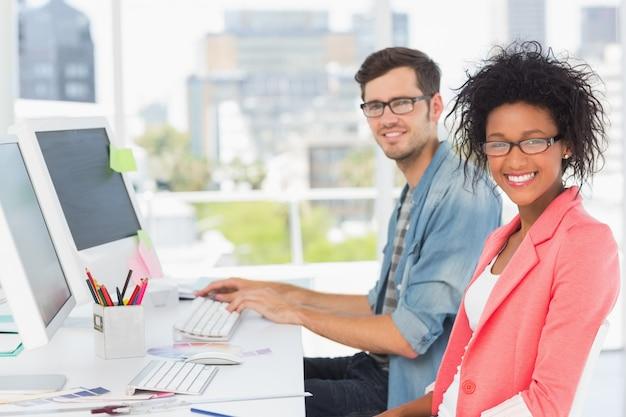 Glimlachend toevallig jong paar dat aan computers in een helder bureau werkt