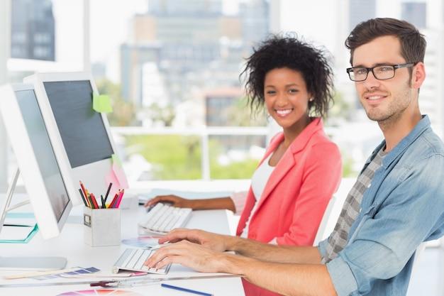 Glimlachend toevallig jong paar dat aan computers werkt