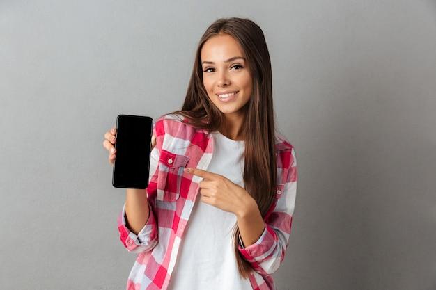 Glimlachend toevallig meisje dat vinger richt op de lege het scherm mobiele telefoon
