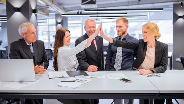 Glimlachend twee jonge vrouwen die elkaar een hoogte vijf in het bureau geven