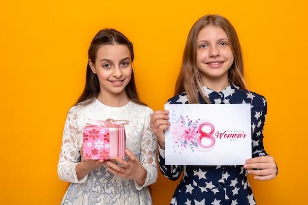 Glimlachend twee kleine meisjes op gelukkige vrouwendag met cadeau met wenskaart