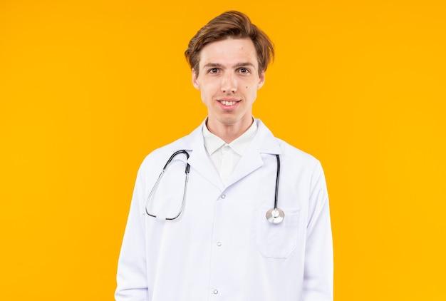 Glimlachend uitziende camera jonge mannelijke arts dragen medische mantel met stethoscoop geïsoleerd op oranje muur