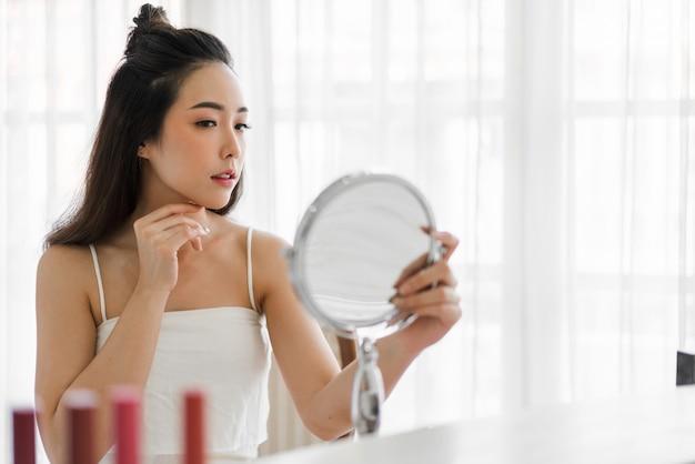 Glimlachend van jonge mooie aziatische vrouw schone frisse gezonde witte huid spiegel kijken. meisje aan te raken op haar gezicht met hand en crème toe te passen thuis. spa en beauty concept