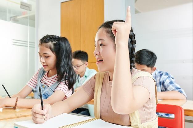 Glimlachend vietnamees schoolmeisje dat hand opheft om vraag over de schooltest te stellen