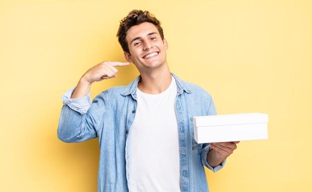 Glimlachend vol vertrouwen wijzend naar eigen brede glimlach, positieve, ontspannen, tevreden houding. witte doos concept