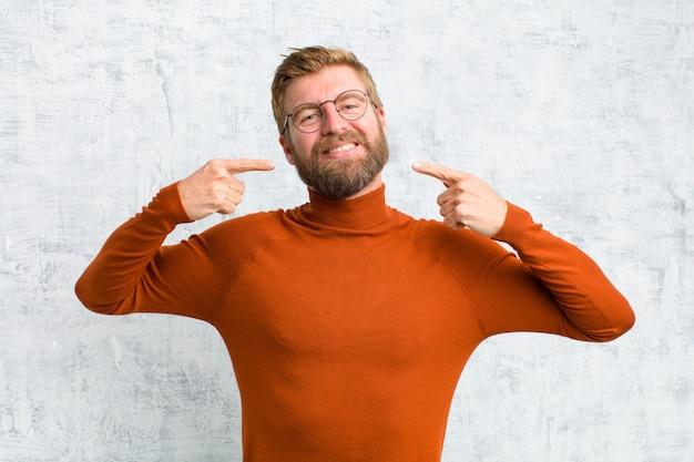 Glimlachend vol vertrouwen wijzend op eigen brede glimlach, positieve, ontspannen, tevreden houding