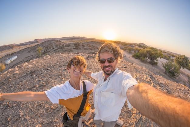 Glimlachend volwassen paar die selfie in de namib-woestijn, het nationale park van namib naukluft, reisbestemming in namibië, afrika nemen. fisheye-weergave in tegenlicht, avonturen in afrika.