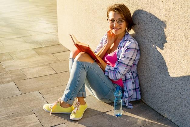 Glimlachend volwassen vrouwelijk drinkwater en het lezen van een boek.