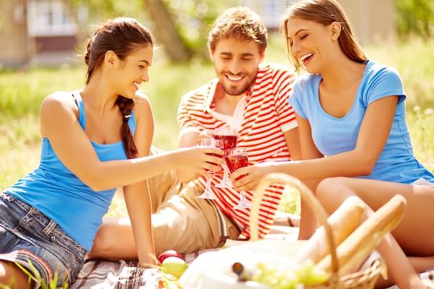 Glimlachend vrienden met picknick op een zonnige dag
